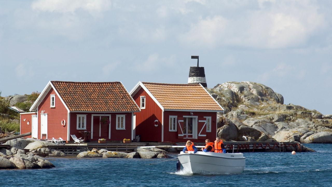 Tre personer i båt i skjærgården på Sørlandet.