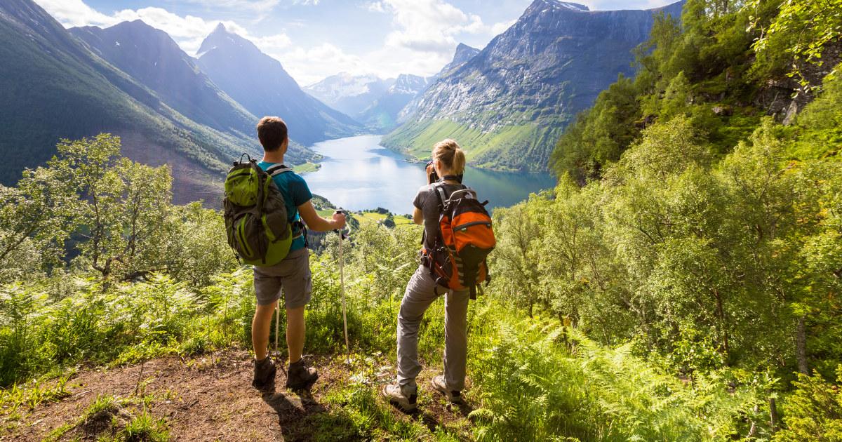 Mann og dame ved utsiktspunkt over en fjord.