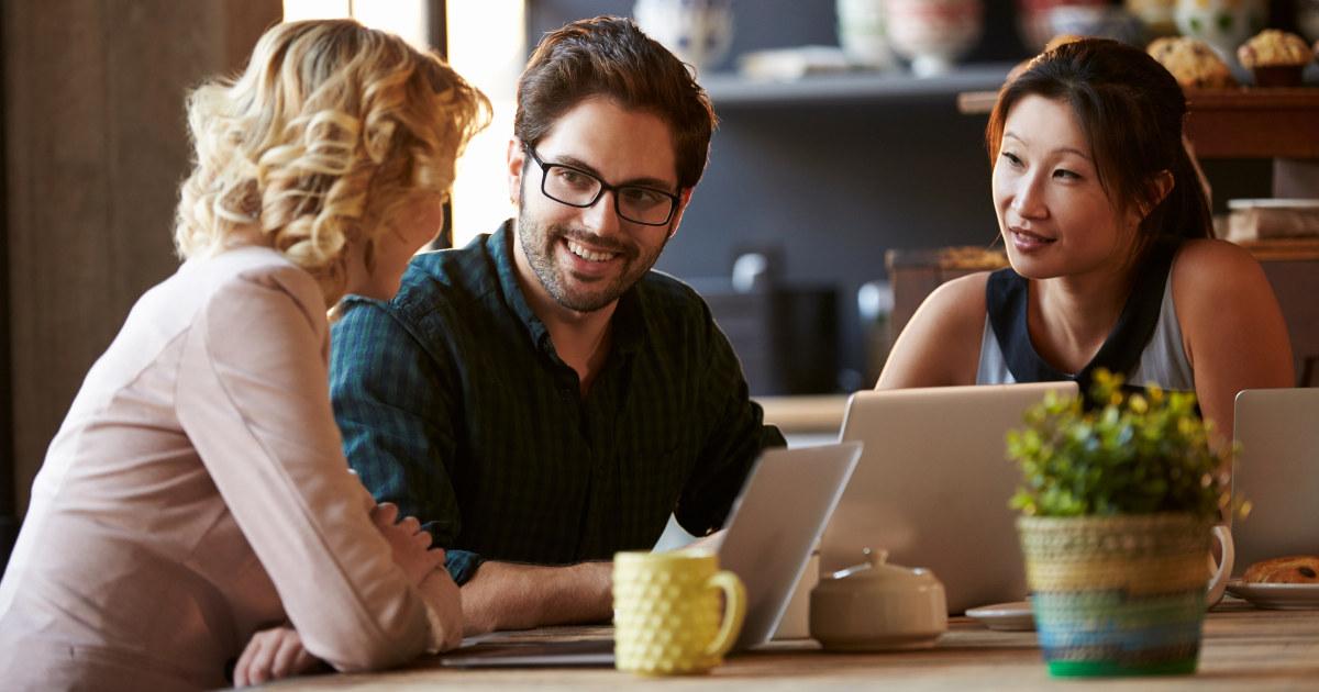 To kvinner og en mann snakker rundt et bord. De har hver sin PC.