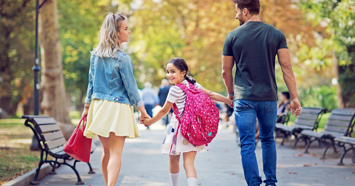 Foreldre følger datter til skolen.