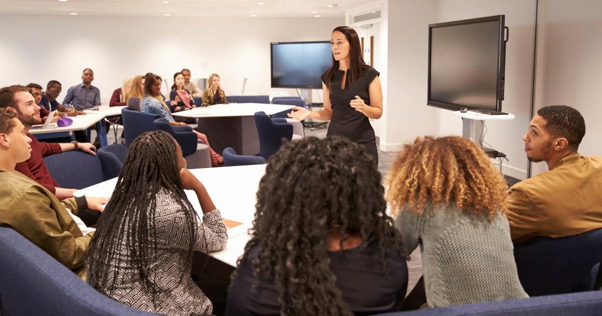 En kvinne underviser voksne som sitter i en halvsirkel rundt i et seminarrom.