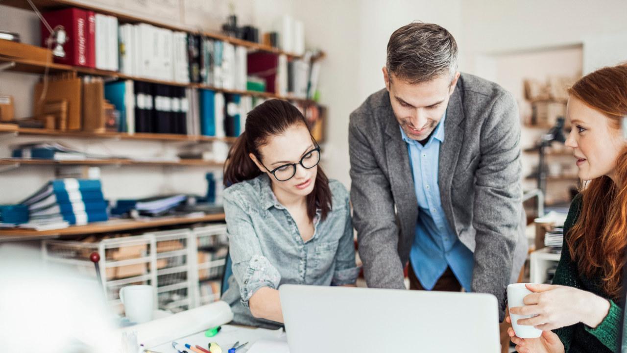 To kvinner og en mann snakker sammen på et kontor foran en datamaskin.
