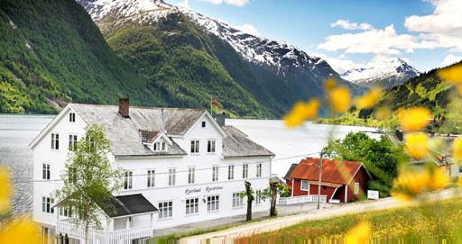 Foto av Fjærland Fjordstove Hotell med fjord og fjell i bakgrunnen