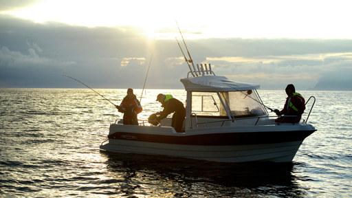 Tre mennesker i båt som havfisker
