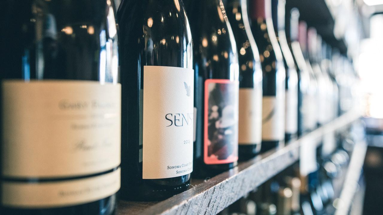 Nærbilde av vinflasker på en hylle