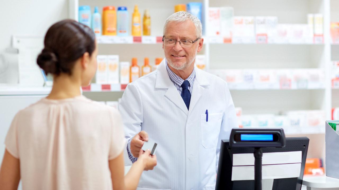 Mann tar i mot kredittkort i et apotek