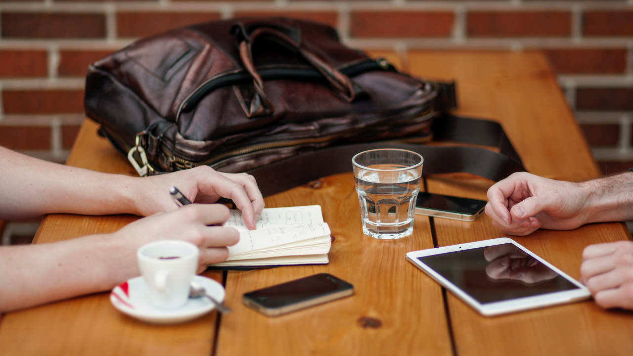 Cafebord med to kaffekopper, en veske, en Ipad og en mobiltelefon