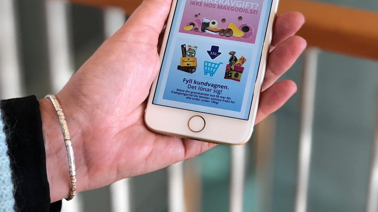 En hånd som holder en mobiltelefon med nettbutikken til Maxigodis åpen.