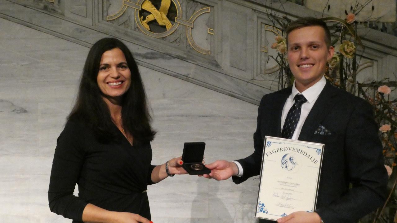 Nina Solli deler ut fagprøvemedalje til Hans Vegar Danielsen i IKT – servicefaget