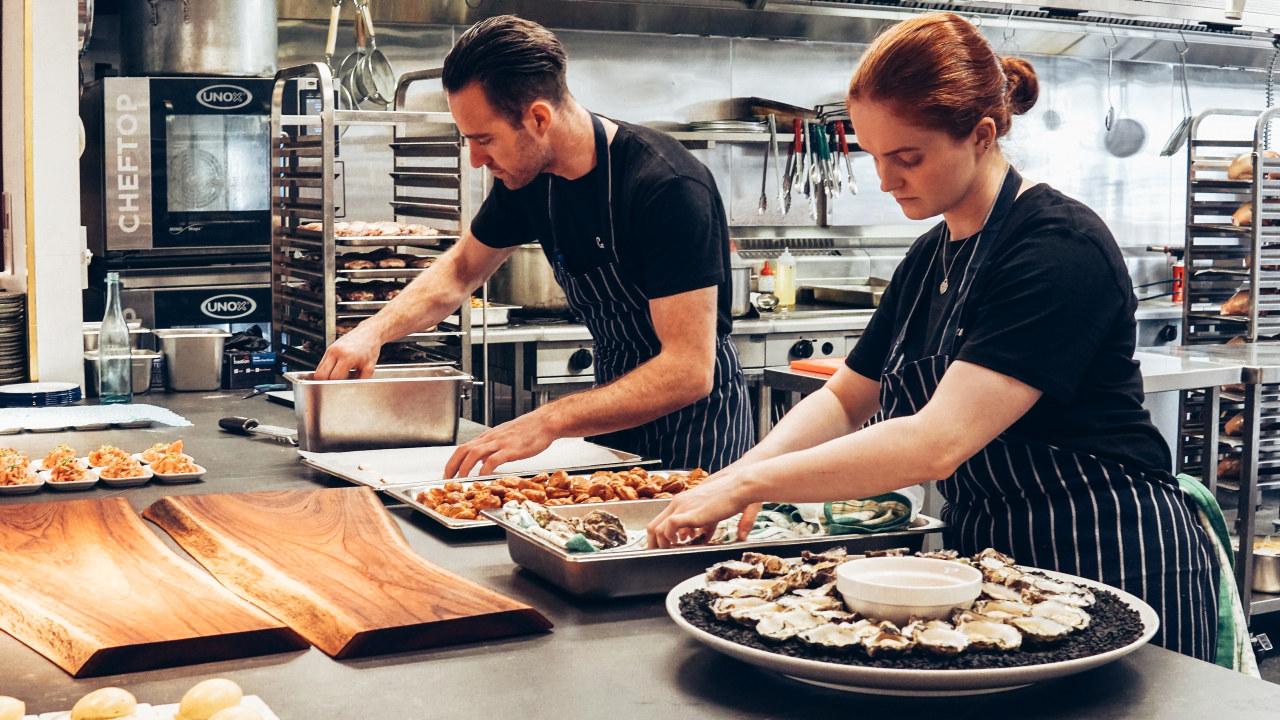 To personer som jobber på et kjøkken