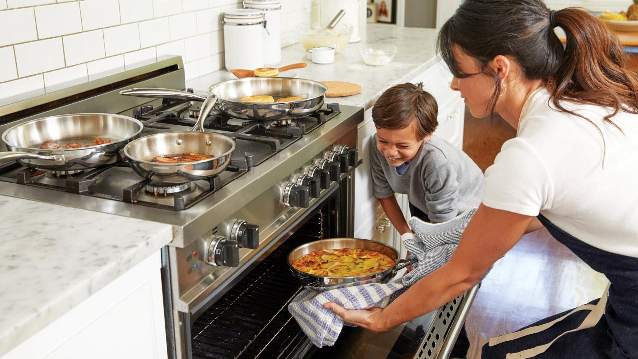 En mor som setter en form med gratinerte poteter i komfyren mens sønnen ser på