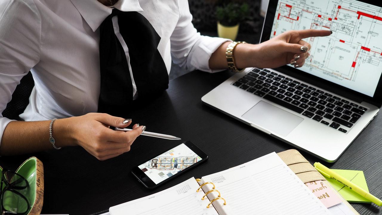 Nærbilde av en som peker på en arkitekttegning på en PC-skjerm