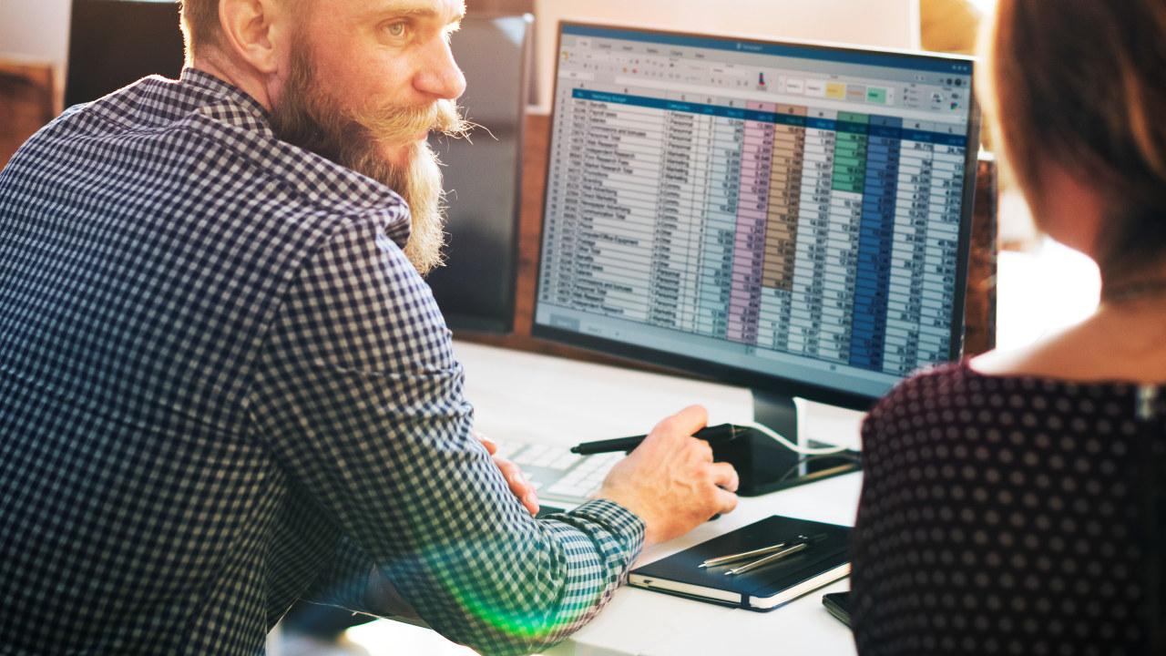 Foto. Mann og datamaskin. Tabeller på skjerm.