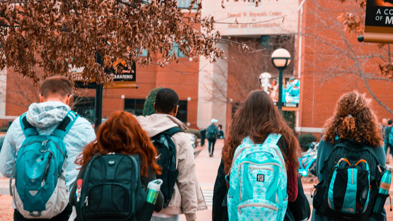 Fire studenter med ryggsekk. Ryggen til kamera.