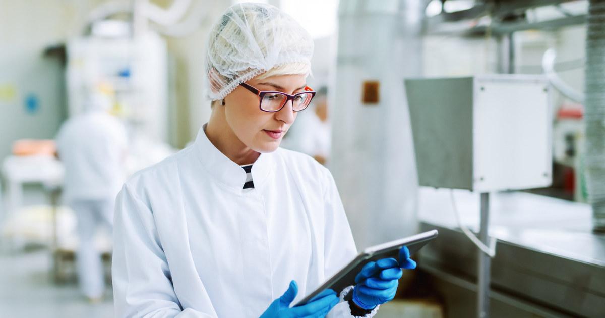 Kvinne i hvite klær inspiserer bedriften med hårnett og hansker. Hun ser på et nettbrett.