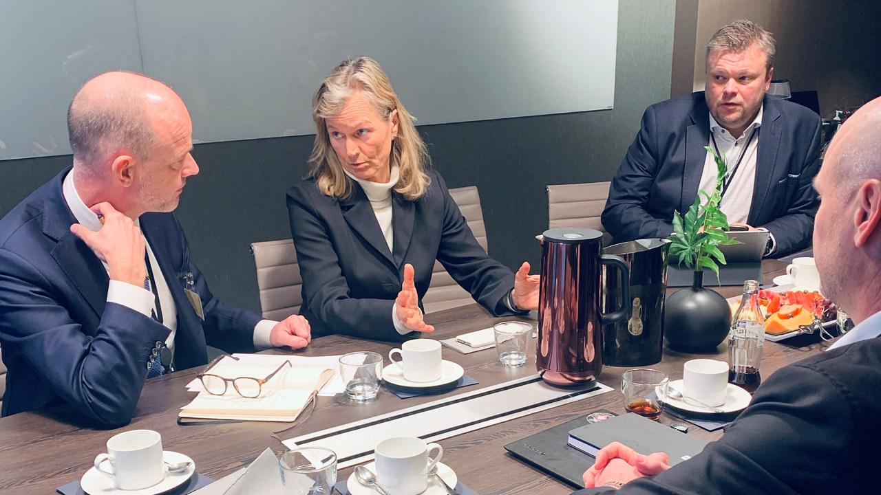 Bildet viser tre menn i dress som sitter rundt et bord og ser på Kristin Krohn Devold, som snakker mot Ole Erik Almlid i NHO. Det er kaffekopper på bordet og notatblokker.