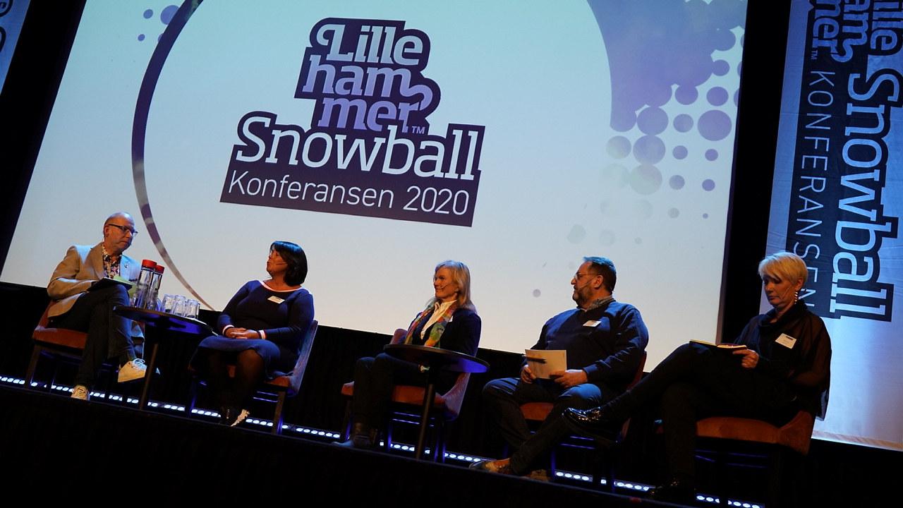 Bilde tatt nedenfra opp mot en scene der fire paneldeltagere sitter og ser mot moderator. I bakgrunnen er en hvit skjerm med teksten Snowball-konferansen.