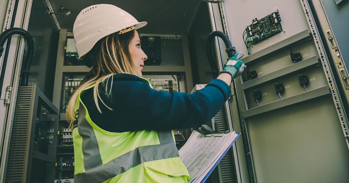 Kvinnelig ingeniør inspiseres et kontrollpanel.