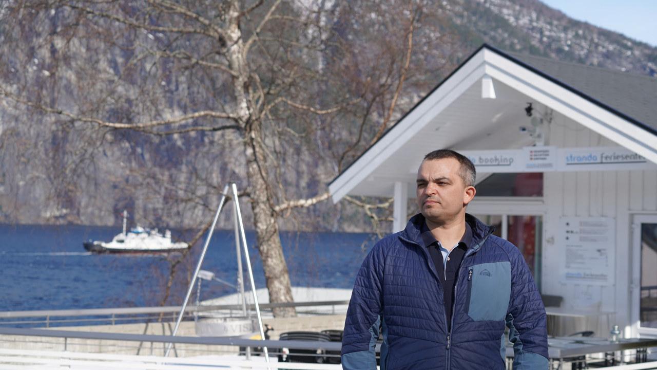 Bilde av en mann i blå jakke med mørkt hår, som står foran en hvit hytte. I bakkgrunnen ser man et fjell, en bålpanne og en ferge som går forbi på fjorden.