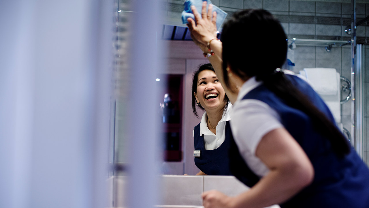 Stuepike vasker speil på hotellrom