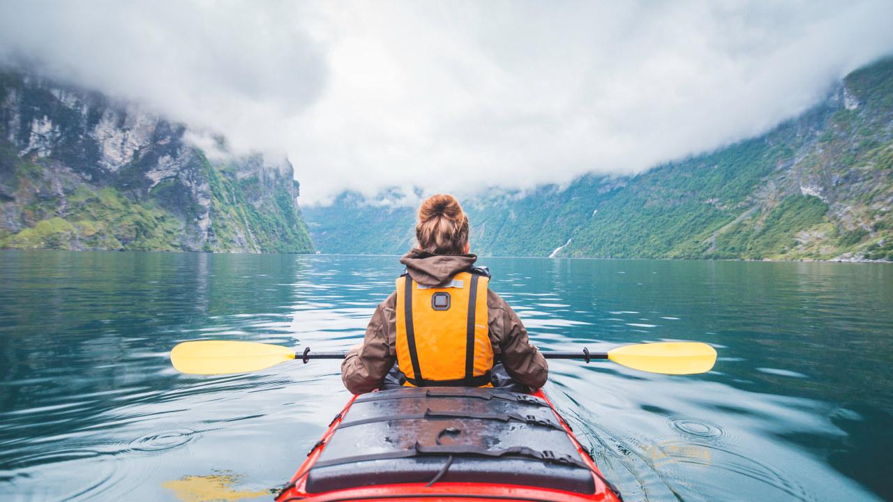 Kvinne som padler kajak i Geirangerfjorden