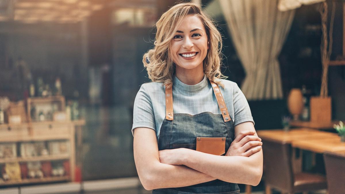 Leder av kafé står og smiler i kamera.