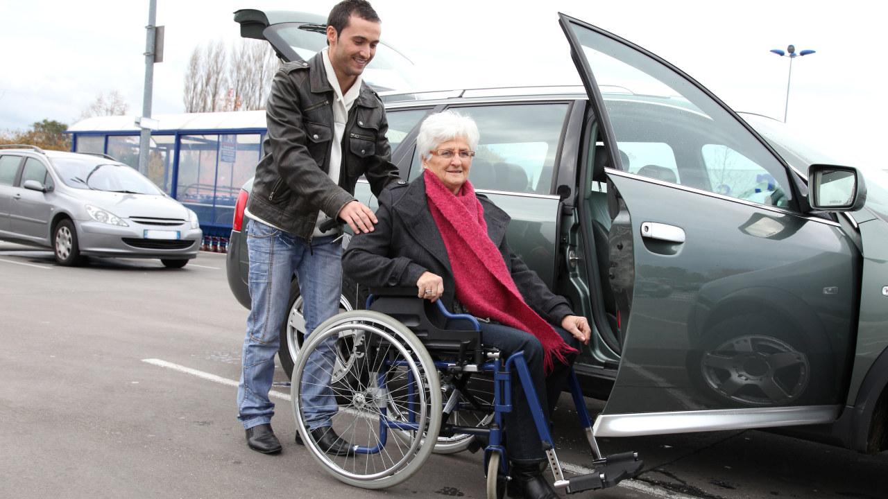 mann hjelper eldre kvinner i rullestol