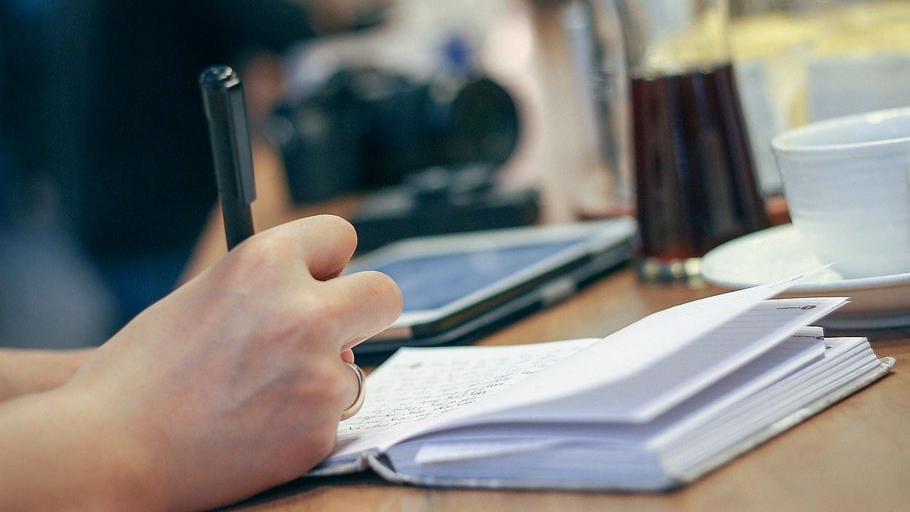 Bilde av en hand som skriver med penn på en tom papirblokk