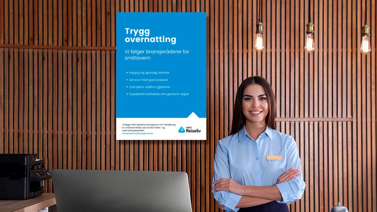 Hotellresepsjon med Trygg overnatting-plakat