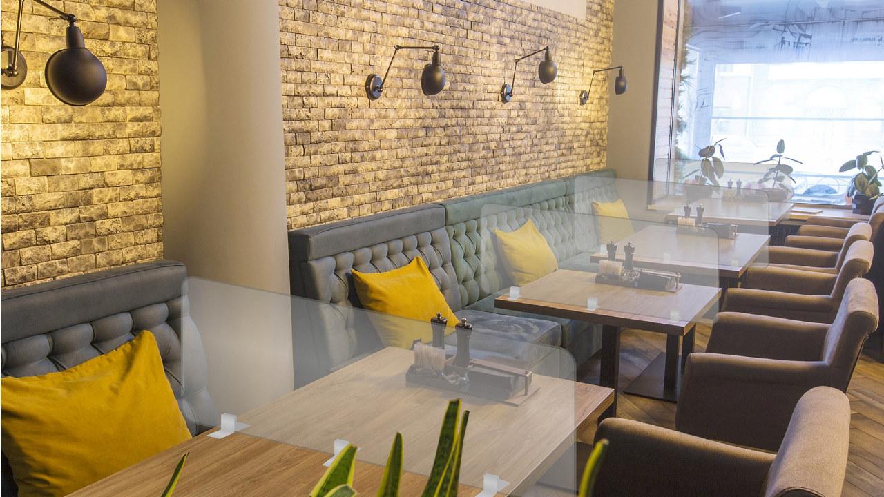 Bilde av en restaurant med skillevegger i akryl montert som smittevern mellom bordsettingene.