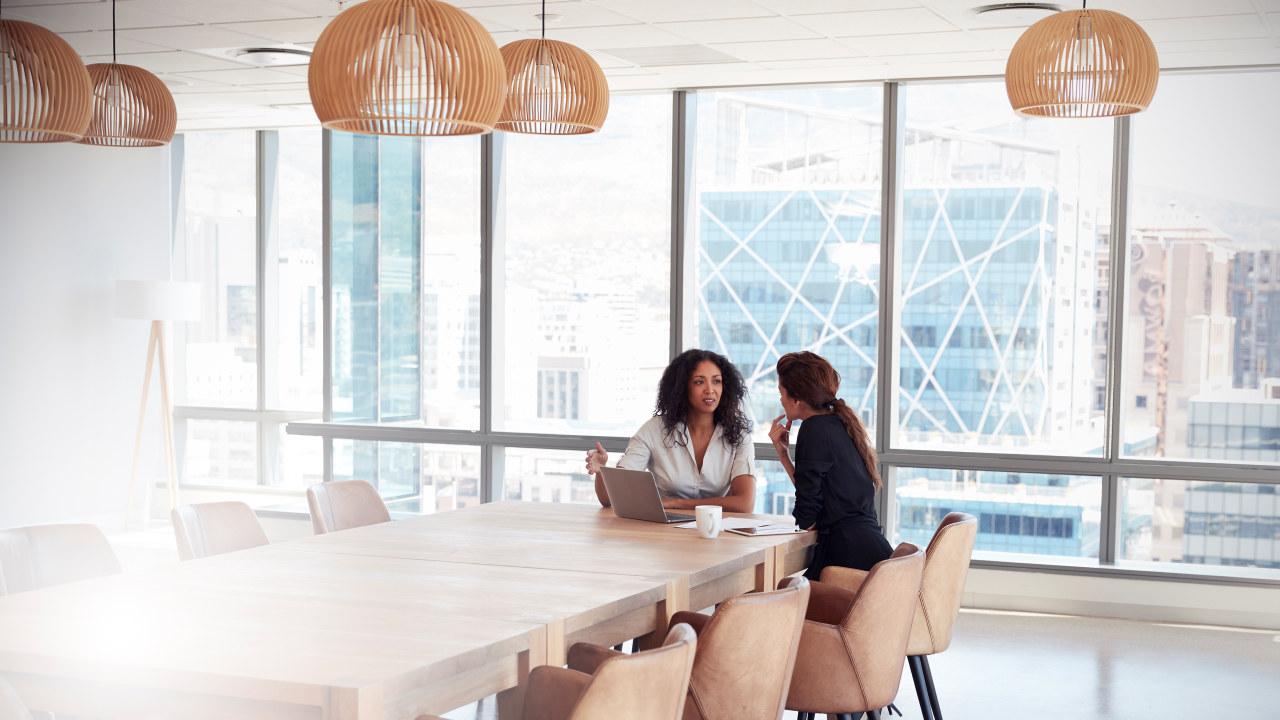 To kvinner sitter ved et møtebord og snakker