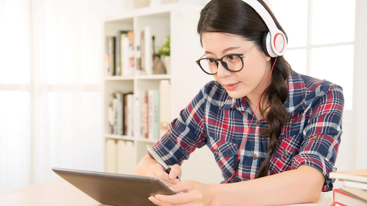 Illustrasjonsbilde av en ung kvinne som studerer ved en skjerm.