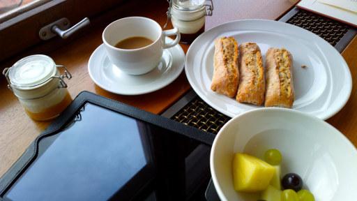 Foto av en kaffekopp, en tallerken med rundstyjjer, en skål med frukt og glasskrukker med yoghurt ved siden av et nettbrett.