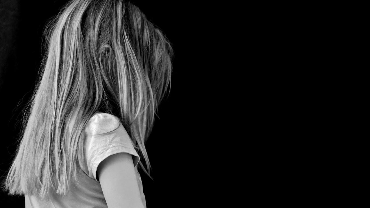 Sort-hvitt-bilde av en uidentifiserbar jente mot en sort bakgrunn.