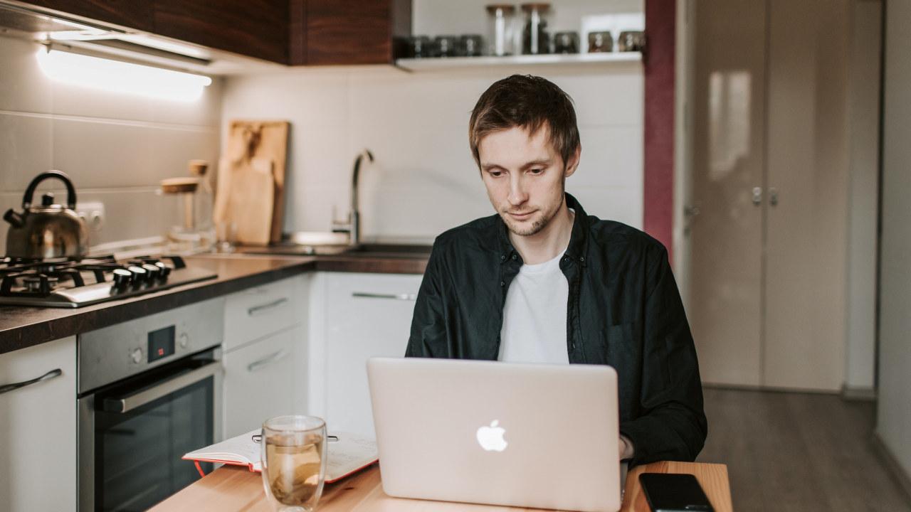 Ung mann sittende forran laptop ved kjøkkenbordet