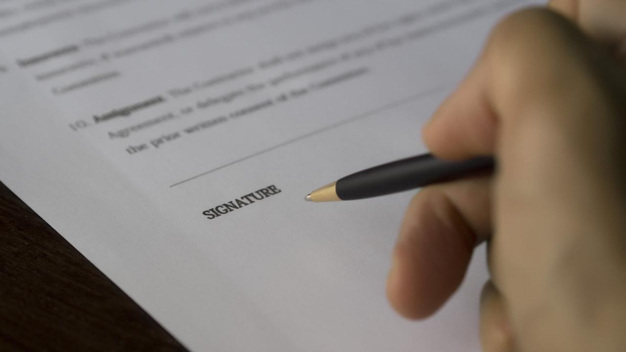 En hånd som skriver under på et dokument