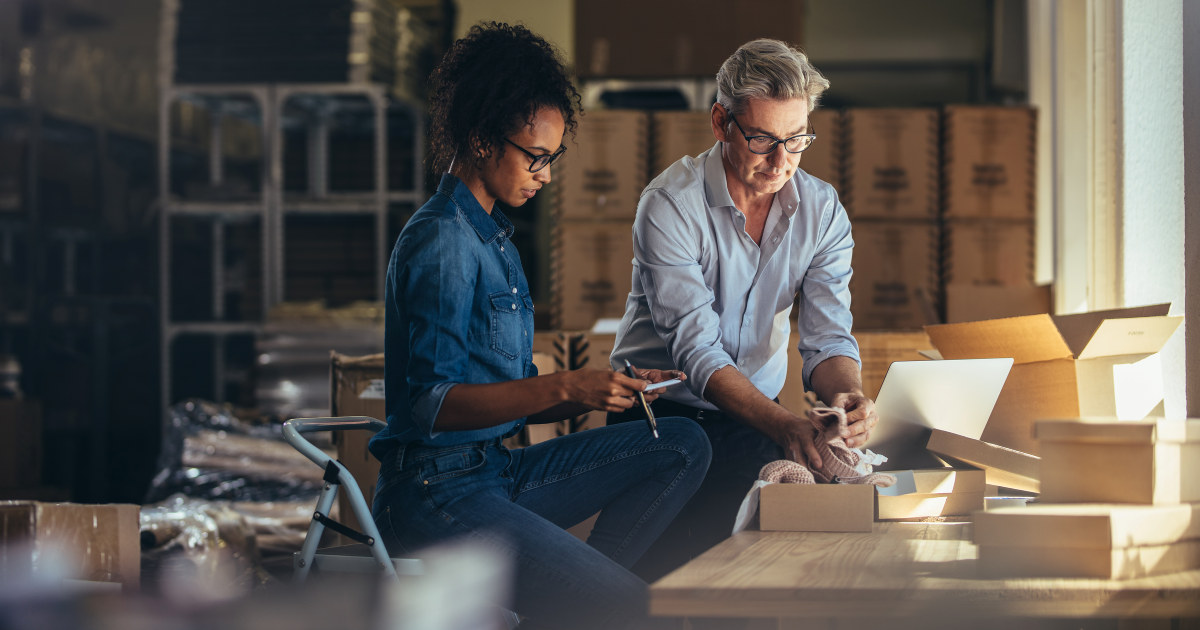 Mann og kvinner jobber med å sortere pakker i en liten bedrift.