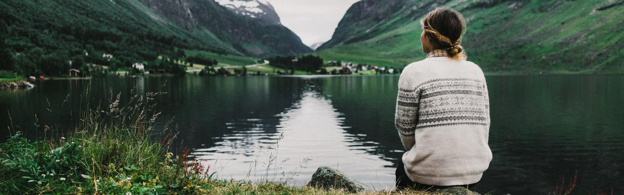 En unge dame i strikket genser sitter og ser utover en innsjø i grønne omgivelser.