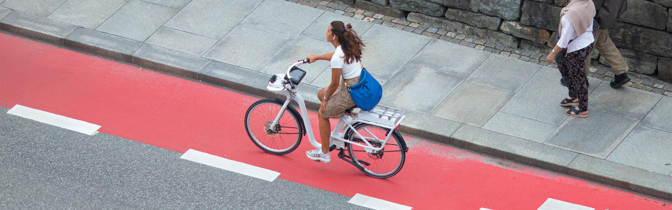 Ung kvinne på elsykkel på sykkelfelt