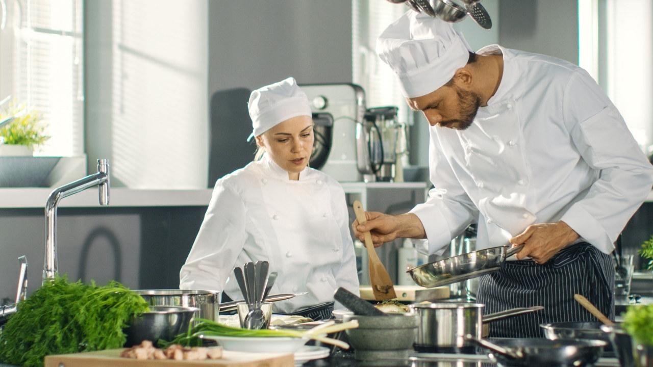 Illustrasjonsbilde av to kokker på et kjøkken.