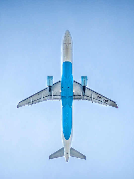 Et bilde tatt under et fly som er på himmelen over kameraet. Blå himmel på alle sider rundt.