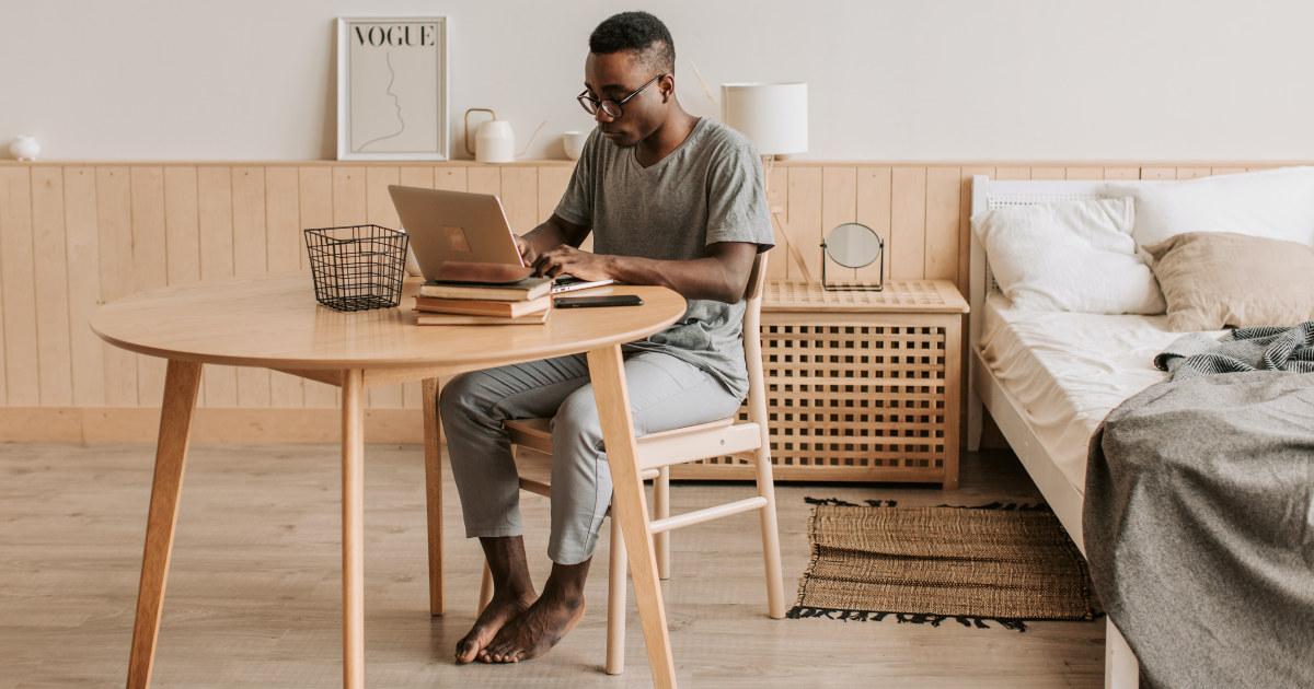 Mann ved bord som jobber på laptop