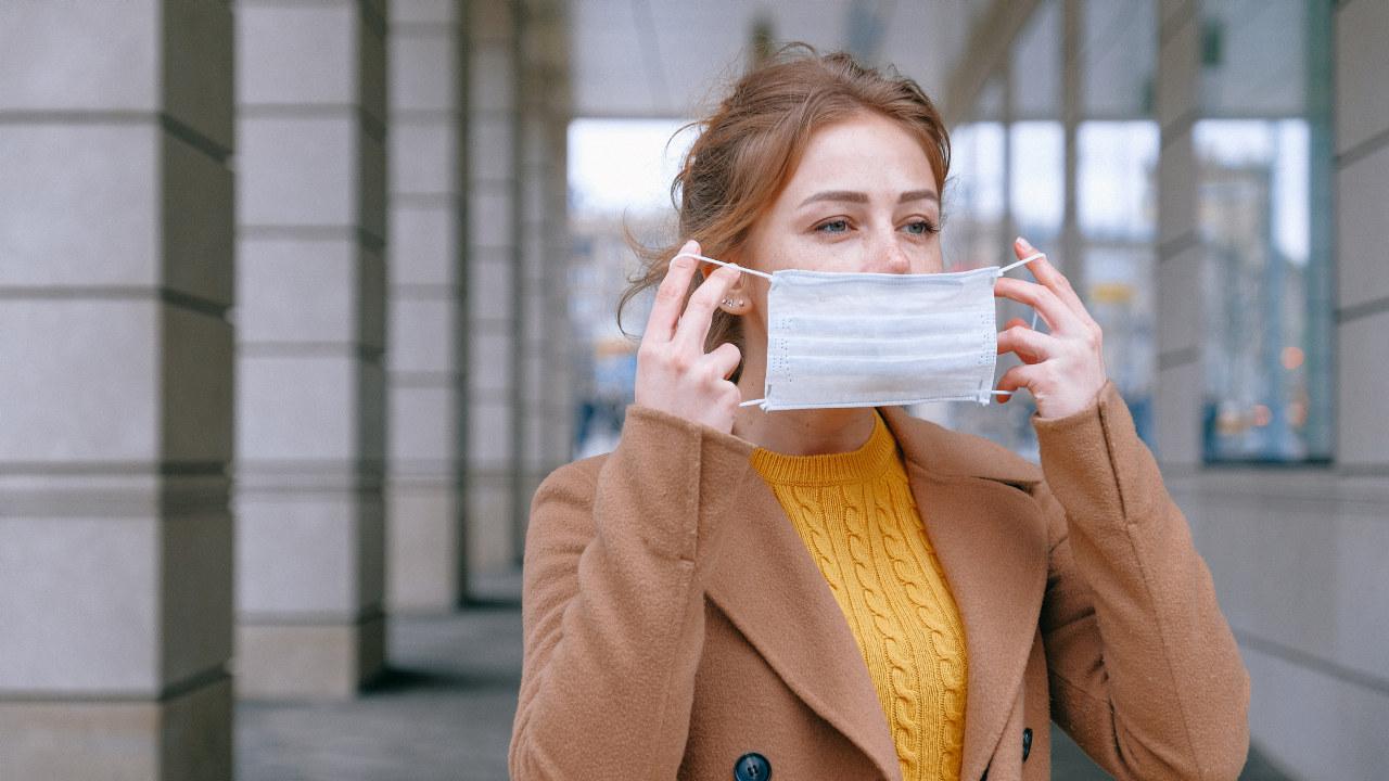 Kvinne som tar på seg et munnbind