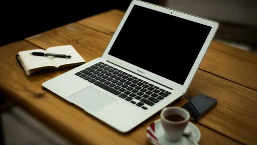 Bilde av et bord med en datamaskin og en kaffekopp på