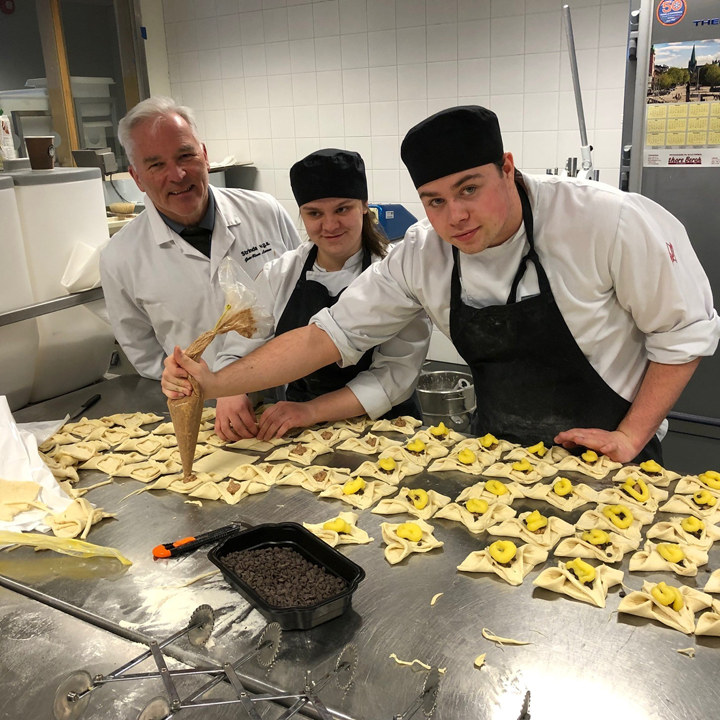 Avdelingsleder for restaurant- og matfag ved Strinda videregående skole, Geir Rune Larsen, sammen med elever på skolen.