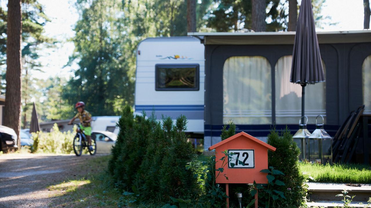 Bilde av campingvogn, liten gutt på sykkel i bakgrunnen.