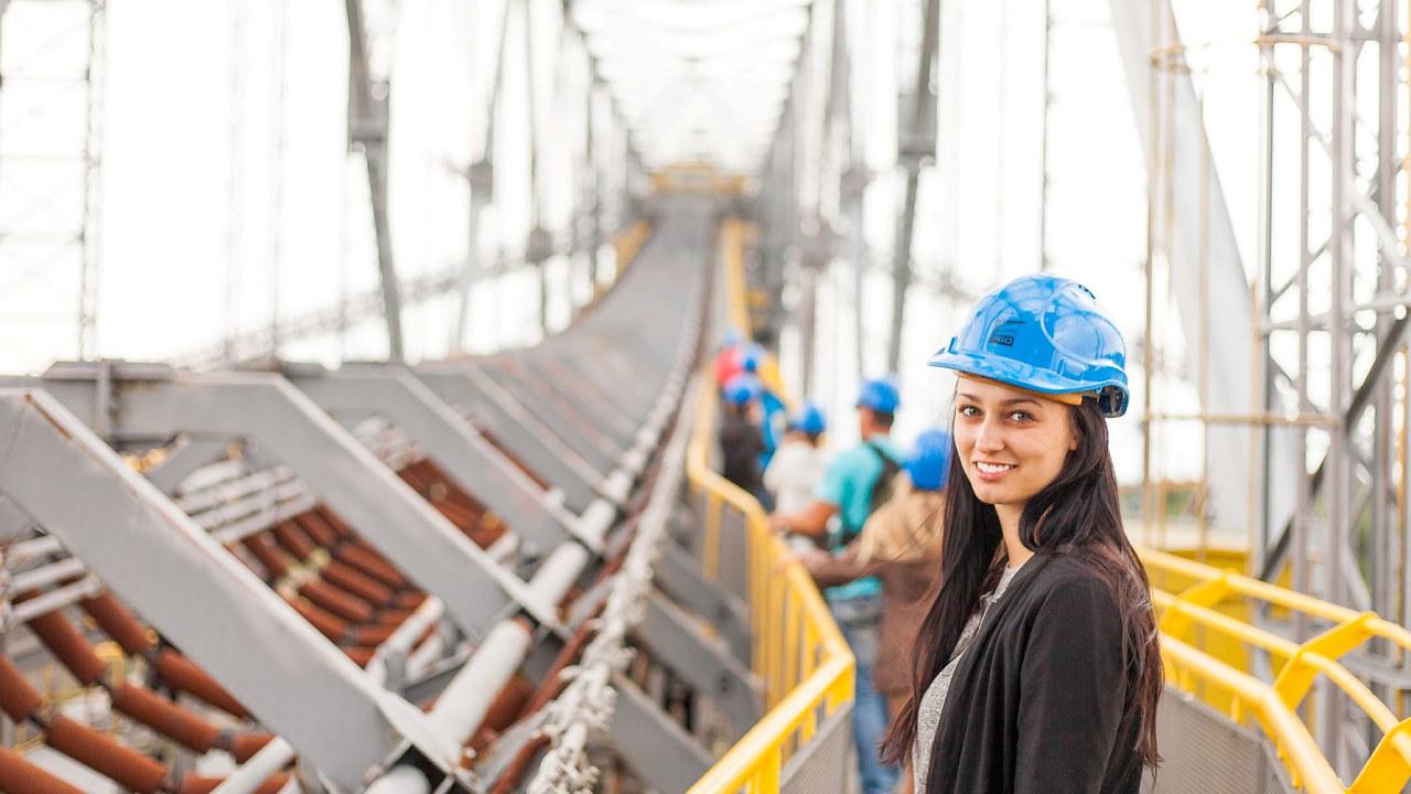 Jente med hjelm stående på bro under konstruksjon
