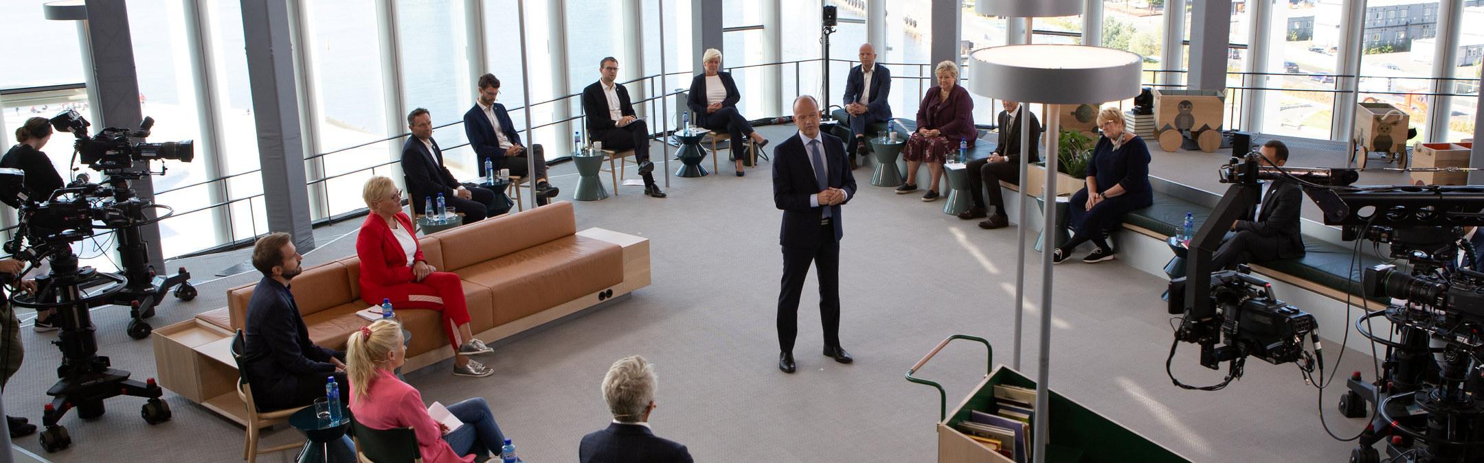 Ole Erik Almlid står med partilederer sittende rundt seg under et NHO arrangement