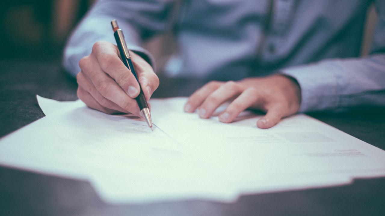 Mann undertegner dokument