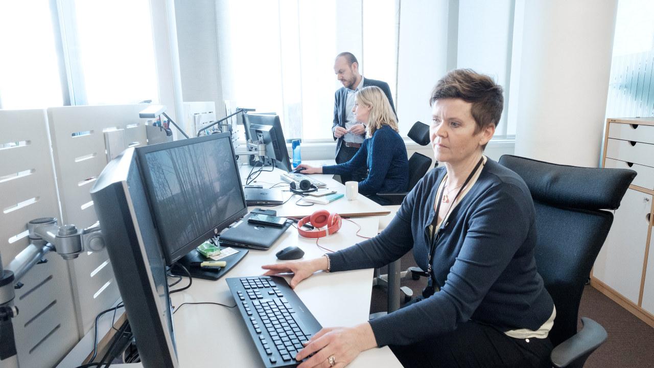 Kvinne ved dataarbeidsplass, en mann og en kvinne som snakker sammen i bakgrunnen